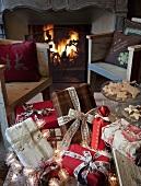 Geschenke mit Schleifenbändern auf einer Bank vor rustikalen Armlehnstühlen und Kaminfeuer