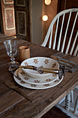 A place setting with stylised edelweiss crockery and mini ski poles on a simple wooden table