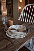 Gedeck mit stilisiertem Edelweissmotiv und Miniatur Skistöcken auf schlichtem Holztisch