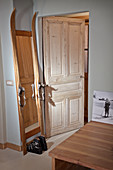 Hand-made, full-length mirror constructed from vintage skis and ski boots next to open door