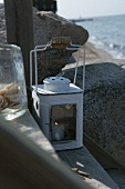Burning candle in white lantern on tread of steps by the sea