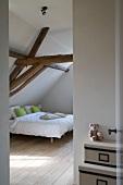 Blick in das Schlafzimmer mit einem Doppelbett unter der offenen Dachkonstruktion