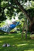 Old man lying in hammock in garden