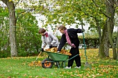 Young couple raking leaves in garden