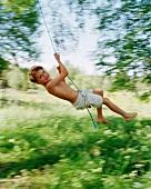 Boy swinging on rope in garden