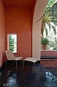 Moderner Stuhl mit passendem Fussschemel aus Korbgeflecht auf schwarzen Steinfliesenboden einer Veranda