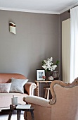 Rustikaler Holzschemel neben altosa gepolstertem Rokokosessel und passendem Sofa vor elegant grau getönter Wand