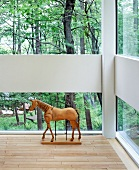 Horse sculpture on floor in front of windows