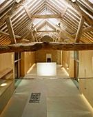 Im Designerstil ausgebauter offener Wohnraum mit Blick in Dachstuhl und auf offenem Küchenbereich