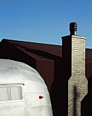 Metal-clad, retro caravan in front of house with black outer shell and chimney