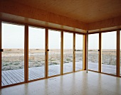 Empty, wood-panelled room with terrace doors and view of landscape