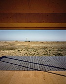 View of flat, coastal landscape across wooden terrace