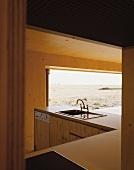 View of kitchen island and open terrace window through open door