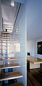 Staircase with wooden treads in front of glass partition in modern living space