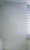 Helle Tapete mit grossem Blumenmuster auf Wand