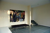 Black couch on large, grey tiles in minimalist foyer