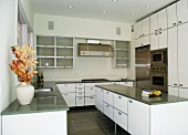 Designer kitchen with central island and white cupboard doors