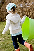 Girl walking in garden holding green basket