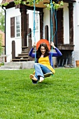 Young woman on swing in garden