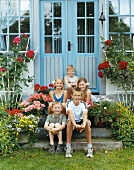 Five children sitting on front step of house