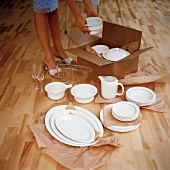 Woman unpacking white porcelain from box