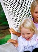 Two girls swinging in hammock