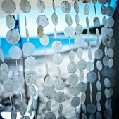 Curtain of discs hanging in a tent at the seaside