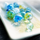 Colourful glass marbles on a tray