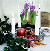 Advent wreath decorated with four burning candles, red onions and cinnamon sticks
