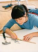 Woman using ruler to measure shelf