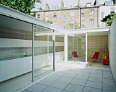 Courtyard with white tiled floor and view of interior through open sliding terrace doors