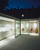 Courtyard with white tiled floor and view of illuminated kitchen and relaxation area through open sliding terrace door