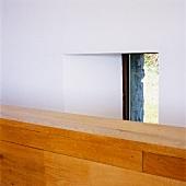 Ausschnitt von einer halbhohen Holzwand vor Fenster