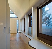Long wall of windows with curved windowsills in modern, open-plan house