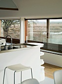 Kitchen island with stainless steel work surface in front of large windows in modern house