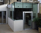 Contemporary glass extension on wooden terrace