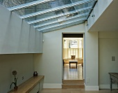 Room in contemporary extension with glass roof and view through open doorway