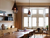 Long wooden table with Bauhaus-era chairs in front of classic bay window