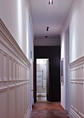 Narrow hallway with white-painted, half-height wood panelling