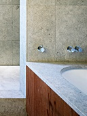 Detail of bathroom with marble cladding on walls and on rim of bathtub