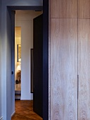 Wooden fitted wardrobe in bedroom next to open door with view of hallway