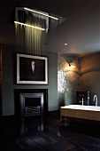 High-ceilinged bathroom with free-standing bathtub and fireplace with dramatic lighting