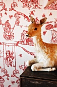 Stuffed fawn on surface in front of wallpaper with erotic pattern