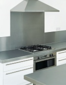 Kitchen unit with gas hob beneath extractor hood