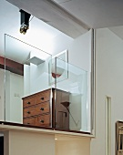 Antique chest of drawers behind half-height glass panels on gallery level