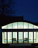 Ein beleuchtetes Poolhaus von aussen