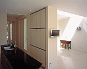 Kitchen island with sink, television mounted on partition wall and console table under skylight