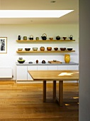Shelves with ceramic bowls and teapots behind dining table