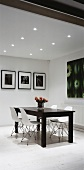 Simple dining room with dark table and white chairs