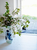 Vase of blossoming twigs on floor